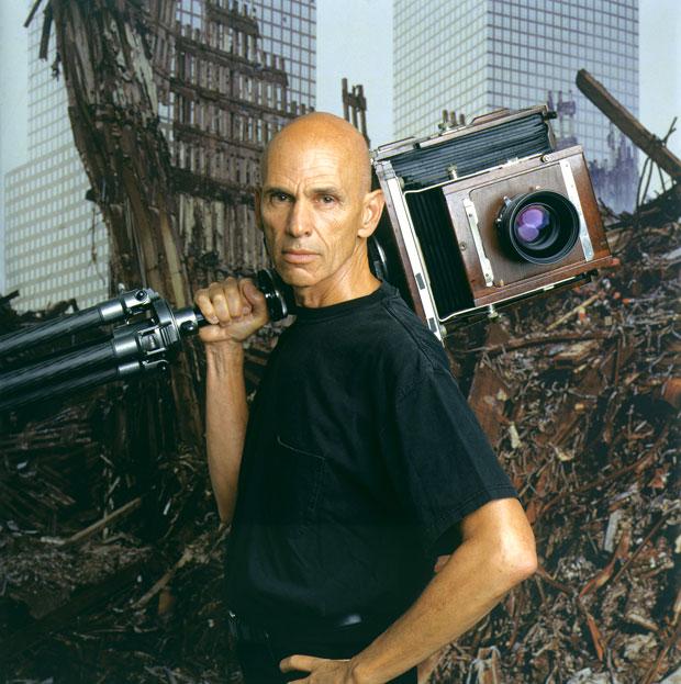 פורטרט של ג'ואל מאיירוביץ עם מצלמת 10*8 . ברקע הריסות מדגלי התאומים