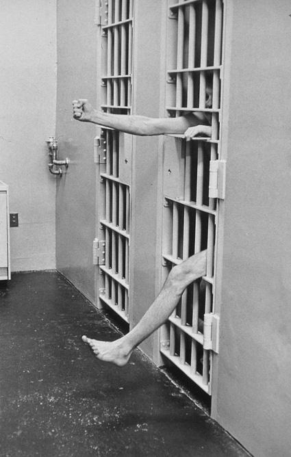 איש בכלא מוציא יד ורגל מבעד לסורגים