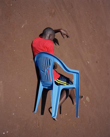 אדם שחור יושב על כיסא פלסטיק על דיונת חול